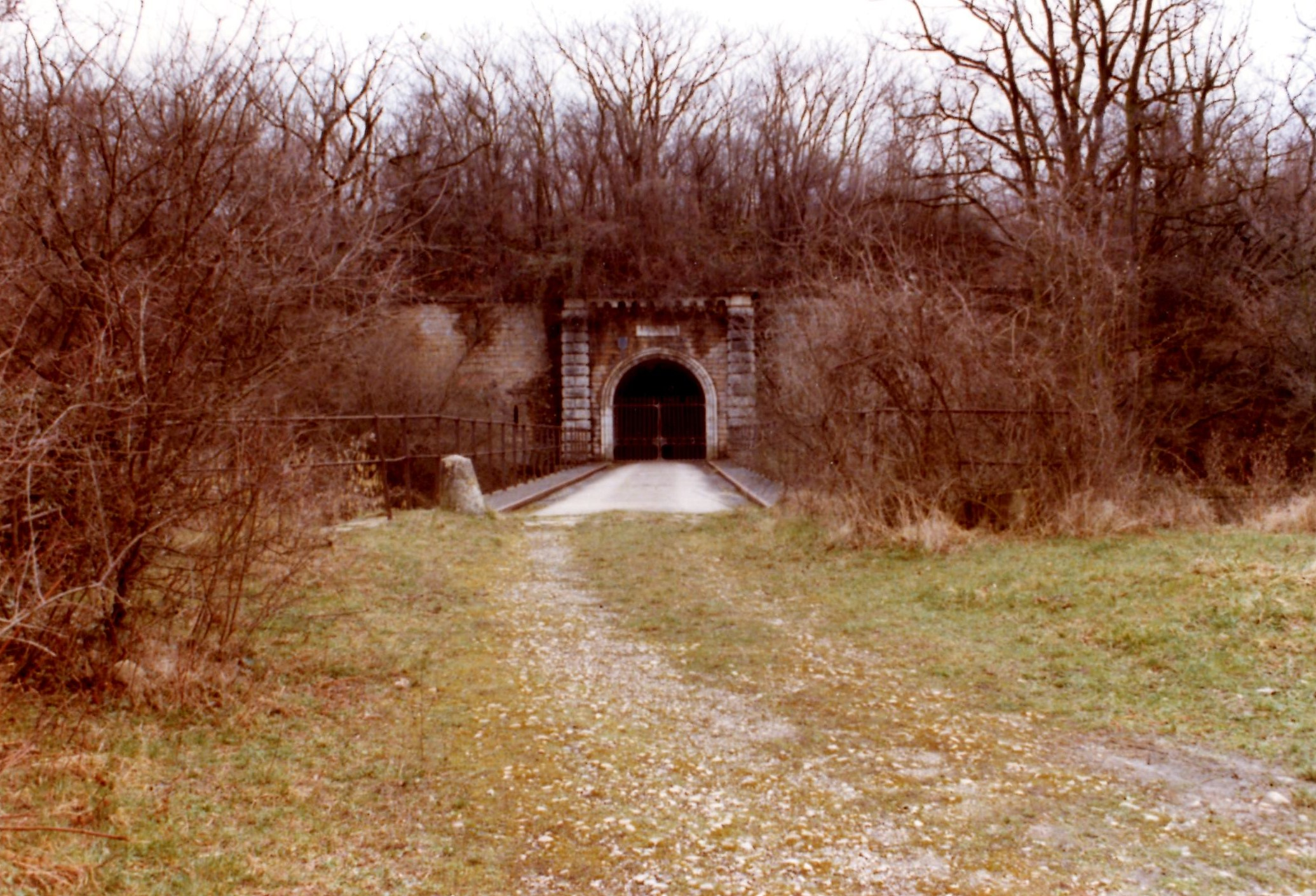 A l'entrée du Fort de Bron en 1978, le pont dormant est caché en partie par la végétation.