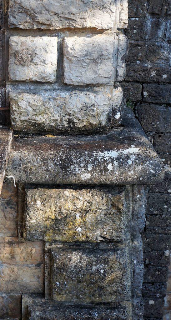 Gros plan sur le support d'un pilastre. Les pierres taillées en bossage sont bien visibles.