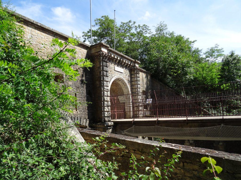Photo prise du chemin de ronde. la photo montre la façade de l'entrée de profil en saillie sur la courtine. Le pont dormant et sa balustrade visibles au dessus du fossé.