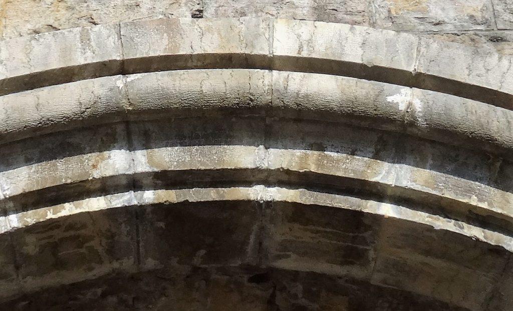 La photo fait un gros plan sur Les pierres taillées en rouleau de la partie supérieure de l'arc en plein cintre.