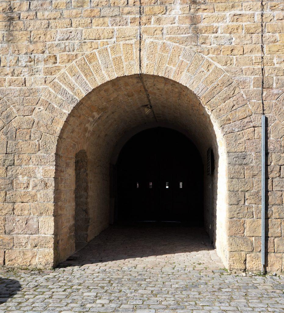 Le vestibule d'entrée vu de la cour du Parados du Fort de Bron. Au premier plan , l'ouverture arrière du vestibule qui s'ouvre dans le mur formé de pierre taillée. Un bel arc autour de l'ouverture.