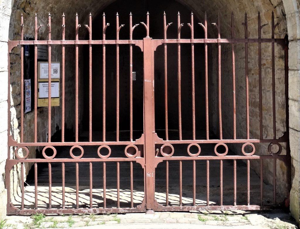 La grille de couleur rouge brique de l'entrée.  Les barreaux sont pointus à la partie supérieure. Une frise horizontale constituée de cercles décore la partie médiane de la grille.
