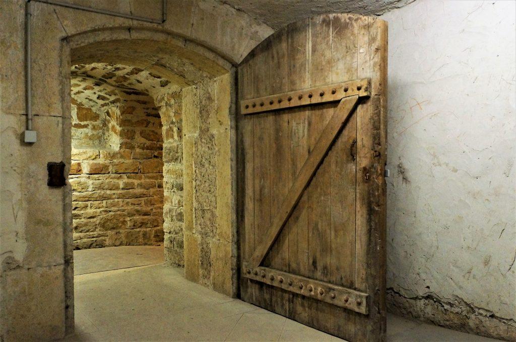Porte d'accès  au vestibule ouverte. Dans le fond une niche est présente dans le couloir d'assainissement.