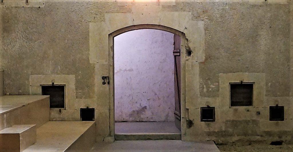 Le mur de la chambre aux poudre montre au centre l'ouverture de la porte d'accès. Sur le bas du mur, on observe les baies d'aréage de la chambre.