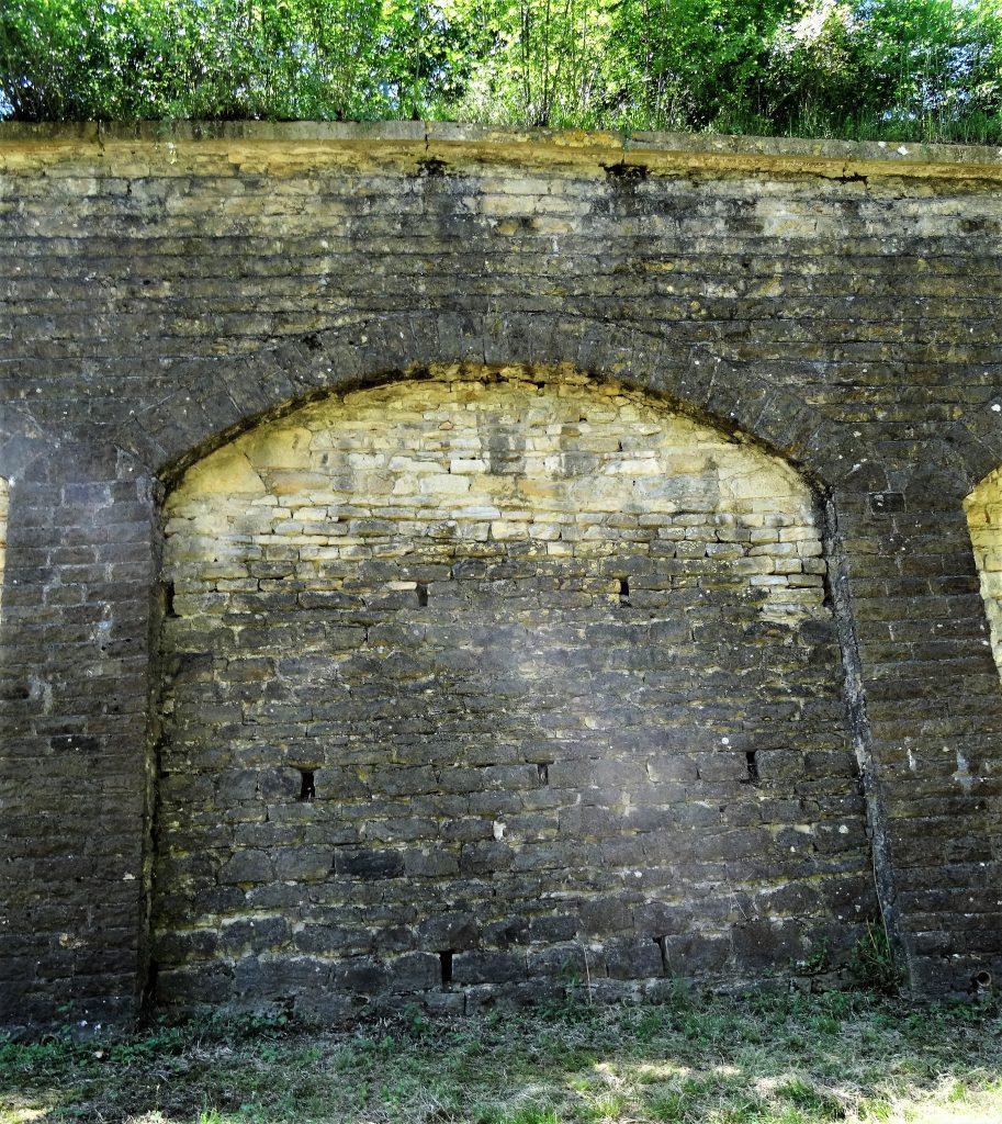 Le mur de masque construit sous les arceaux du mur de contrescarpe est percé d'orifices permettant l'évacuation de l'eau du talus.