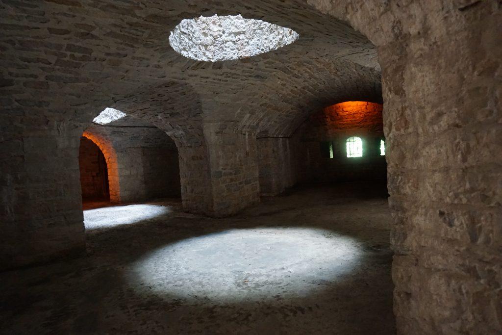la double  caponnière du fort de Bron montre des voutes en berceau. Au plafond, la lumière est apportée par de grandes ouvertures ronde. Sur le mur du fond on aperçoit les embrasures donnant sur le fossé diamant.