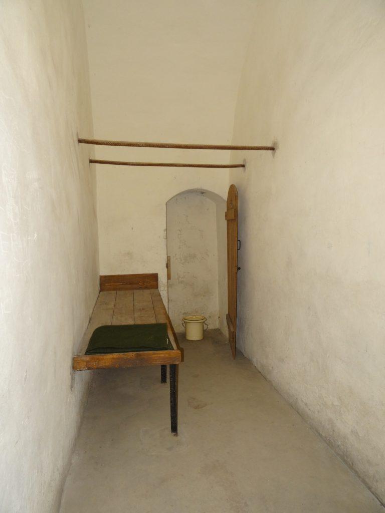 Une cellule des locaux disciplinaires avec son réduit pour le baquet de propreté.