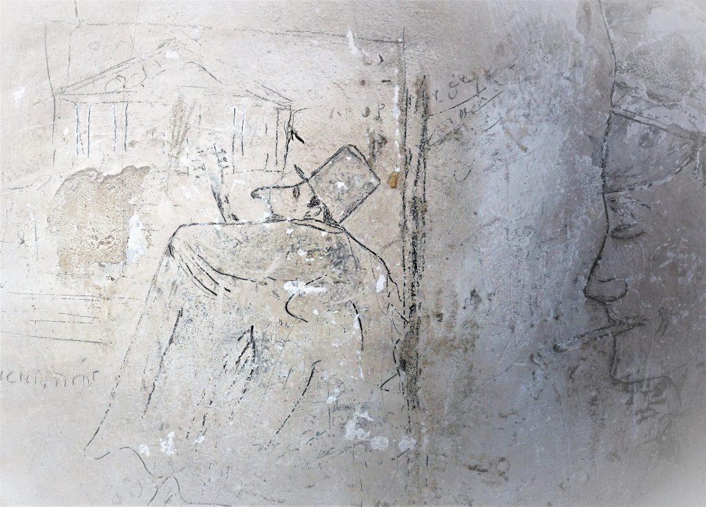 Graffiti montrant deux personnages gravés sur le mur de la salle de police.